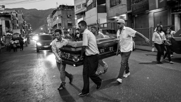 Parientes de Fredy Guerrero, un joven de 35 años torturado y asesinado por la Policía, trasladan su ataúd en el barrio de Catica (Caracas)