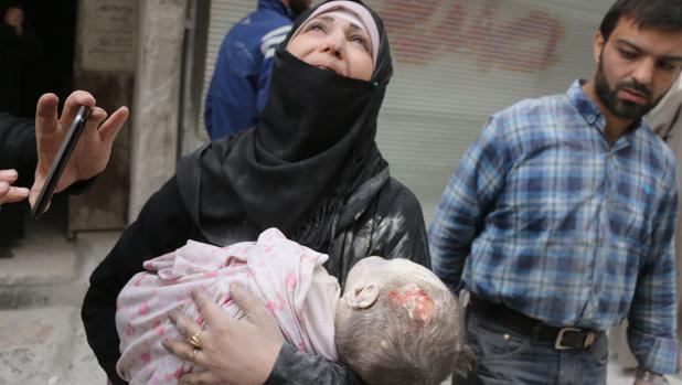Una mujer siria, desesperada, carga el cuerpo de su bebé rescatado de los escombros, tras el bombardeo sobre el área al-Muasalat, en Alepo