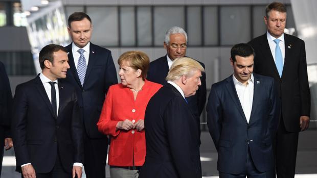 El presidente de los Estados Unidos, Emmanuel Macron, y la canciller alemana Angela Merkel (2ª I) hablan mientras el presidente estadounidense Donald Trump (C) llega junto al primer ministro griego, Alexis Tsipras, para una foto de familia durante la cumbre de la OTAN