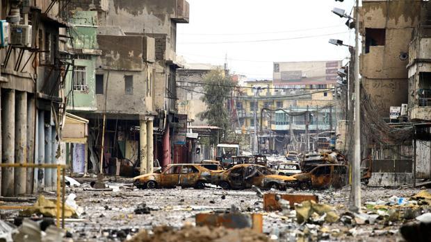 Coches y viendas destruidas tras un enfrentamiento entre soldados del Ejército iraquí y del Daesh