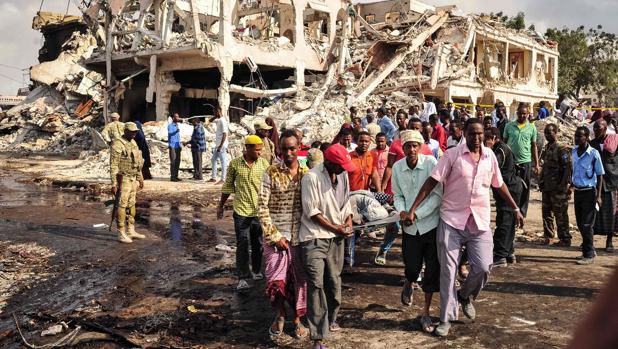 Unos hombres portan a una víctima de un atentado con camión bomba en Mogadiscio (Somalia) el pasado octubre