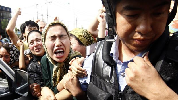 Manifestantes pertenecientes al grupo minoritario musulmán uigur se enfrentan con la policía