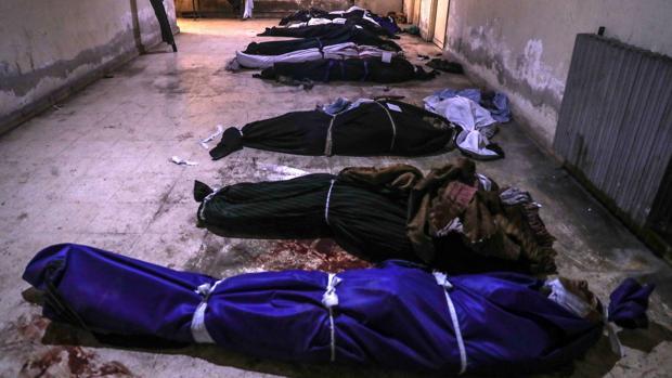 Cadáveres cubiertos con mantas permanecen en una morgue de Duma en Siria