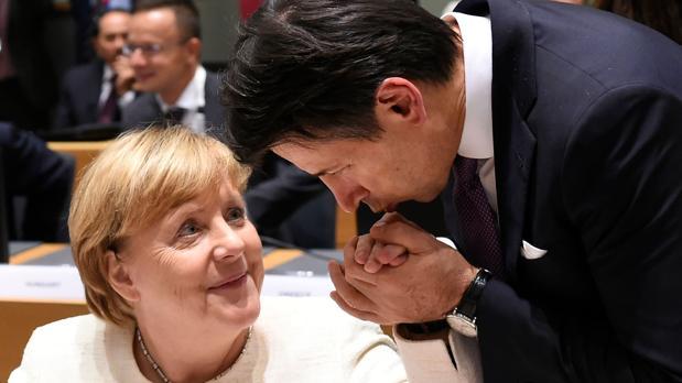 El primer ministro italiano, Giuseppe Conte, besa la mano de la canciller alemana, Angela Merkel, este jueves