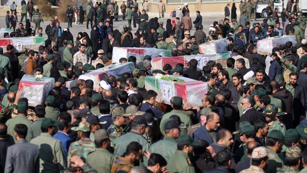Iraníes cargando los ataúdes de las víctimas de un atentado suicida con bomba en un autobús de la Guardia Revolucionaria en el sureste de Irán