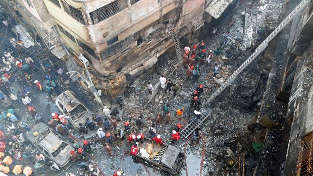 Varios bomberos inspeccionan los escombros tras el incendio