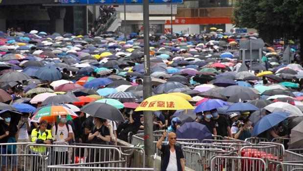 Ante un mar de paraguas, un hombre sostiene uno donde se puede leer: «Por la libertad y contra la malvada ley de extradición a China»