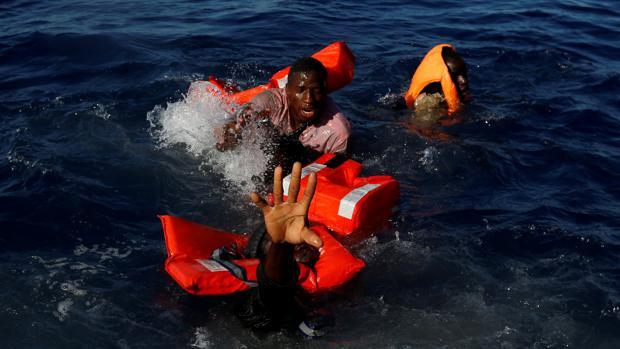Tres tratan de mantenerse a flote tras el naufrafio de su embarcación en las costas de Libia, en 2017
