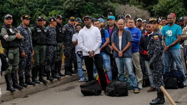 Efectivos de la Policía colombiana custodian a los ciudadanos liberados en la frontera entre ambos países