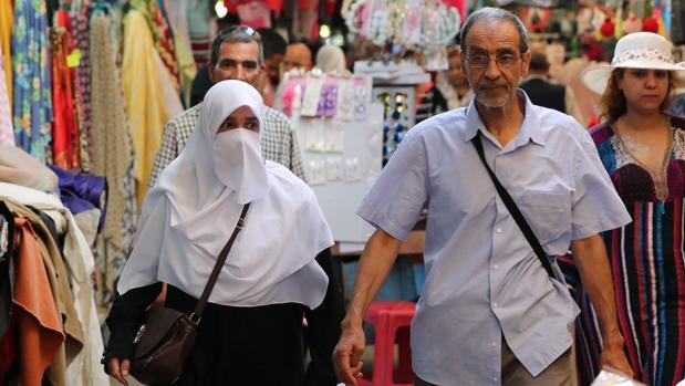 Una mujer con el rostro cubierto con un velo camina por la ciudad vieja de Túnez