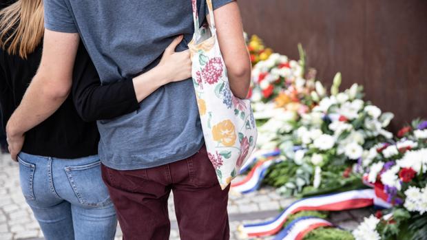 Una pareja permanece de pie frente al memorial del Muro, hoy en Berlín