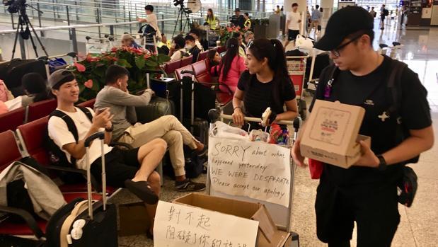Cheung (en el centro) reparte pasteles y agua entre los pasajeros atrapados en el aeropuerto de Hong Kong por los vuelos cancelados por las protestas