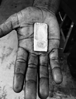 Un hombre muestra una barra de oro fundida
