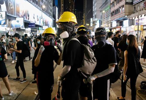 Ataviados de negro, los manifestantes desafían la prohibición de llevar máscaras en la zona comercial de Causeway Bay. PABLO M. DÍEZ