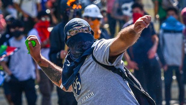 Un manifestante lanza una piedra contra los agentes antidisturbios este lunes en Santiado de Chile