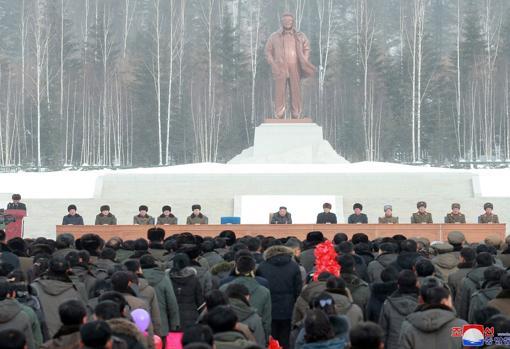 El líder norcoreano sentado con altos cargos de su Gobierno debajo de la estatua de su padre