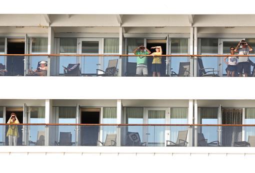 Pasajeros del Zaandam se asoman a los balcones mientras aguardan su futuro