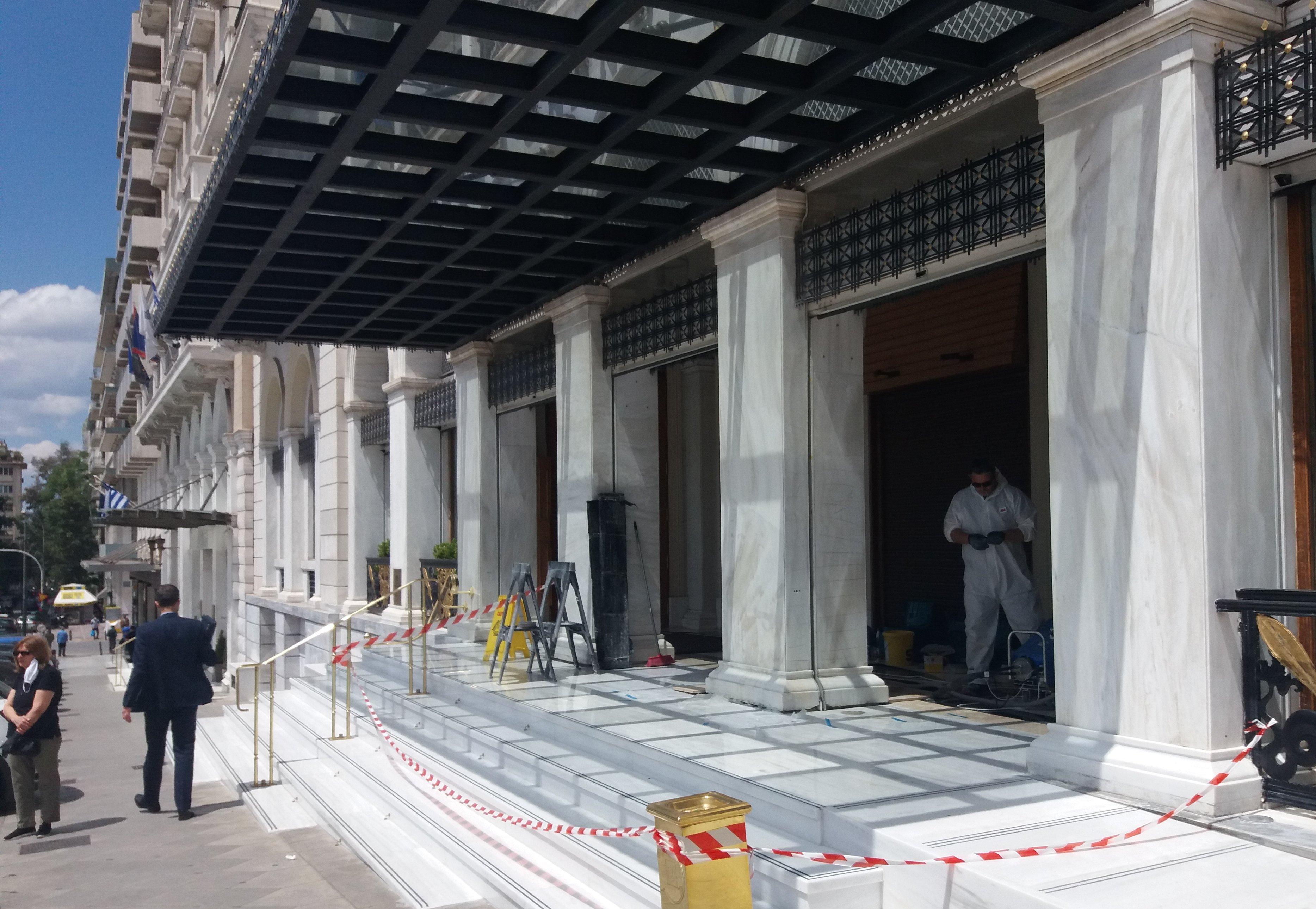 Operarios puliendo el mármol de la entrada del hotel grande Bretagne en la Plaza de la Constitución de Atenas