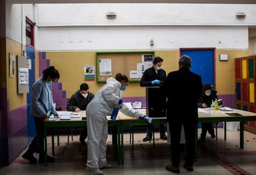 Una mujer, con traje protector, se ocupa de desinfectar un colegio electoral en Lisboa