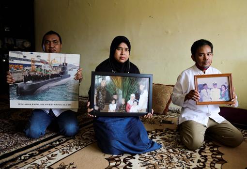 Familiares de los desaparecidos en el submarino muestran fotos de los desaparecidos