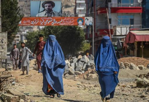 Two women in burqa walk down a Kabul street in front of a sign with the image of the former Afghan commander Ahmad Shah Massoud