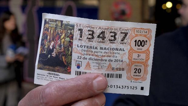 Un empleado del museo de cera de Madrid muestra un boleto de primer premio en la Lotería de Navidad de España en 2014