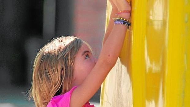 Una niña deposita la bolsa de la basura (con briks, latas, envases de plástico) en el contenedor amarillo