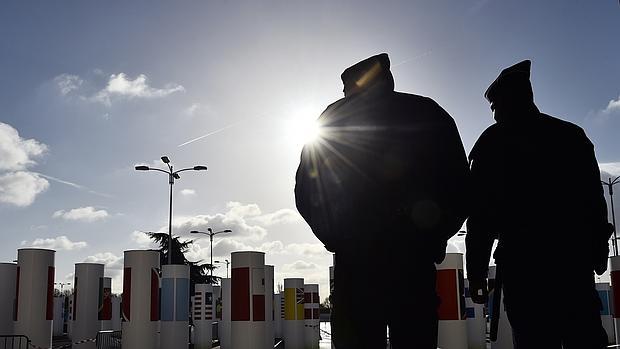 Dos policías franceses hacen guardia frente a la entrada del salón de la COP 21, este jueves