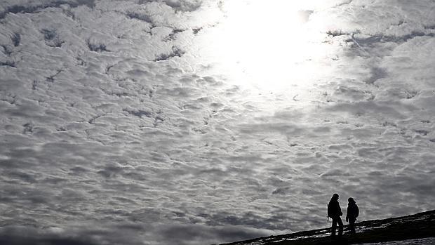 Dos personas caminan por la ladera de la montaña en el alto de Ibañeta, en una jornada en la que el ascenso de temperaturas en Navarra ha sido la nota caracteristica del día