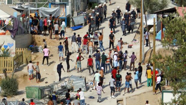 Varios refugiados huyendo del campamento instalado en Moria (isla de Lesbos, Grecia) incendidado este lunes