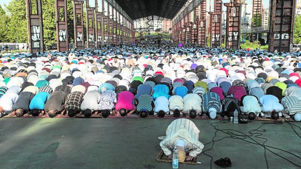 Musulmanes durante la hora del rezo en un parque de Turín