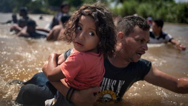 Una niña, inmigrante de Honduras, en brazos de su padre, cruza el río Suchiate, frontera entre Guatelama y México