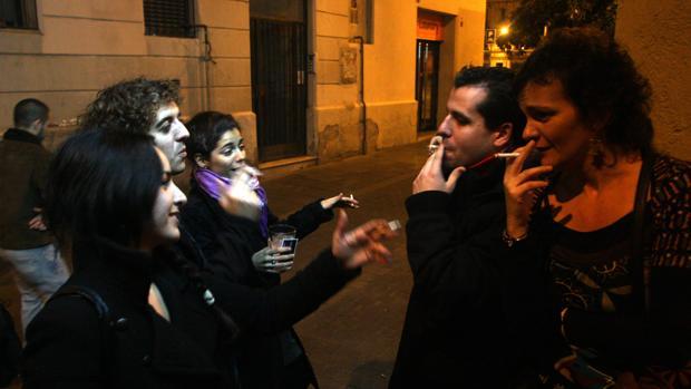 Jóvenes fumando en la puerta de un bar