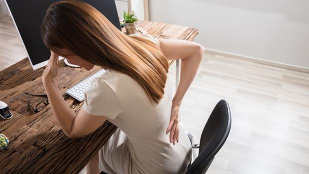 Imagen de archivo de una mujer, frente al ordenador, con dolor de espalda