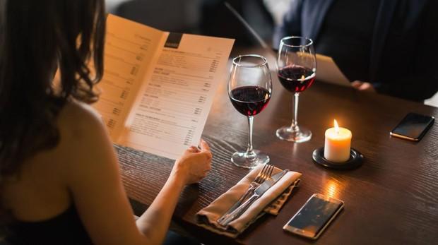 Una pareja examina la carta en un restaurante con dos copas de vinos sobre la mesa